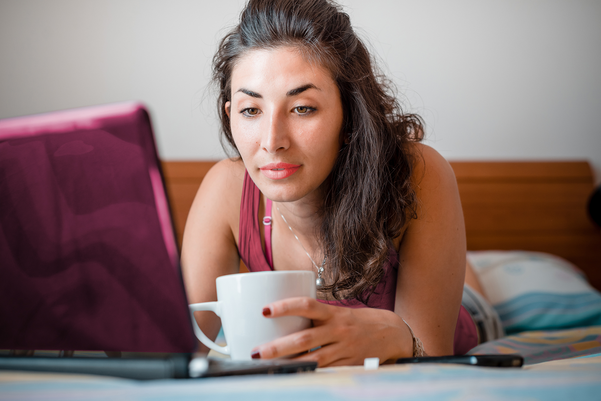 Woman with coffee in front of laptop